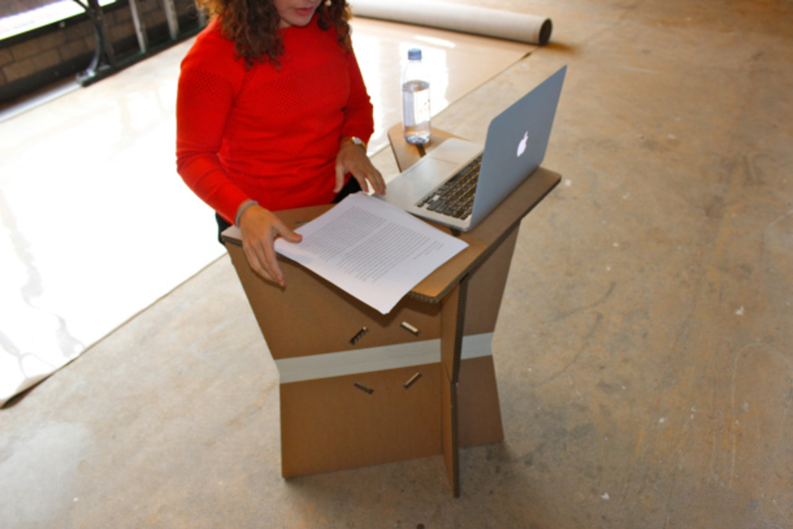 Amanda stands at the cardboard podium, testing its dimensions for her height and surface area needs.