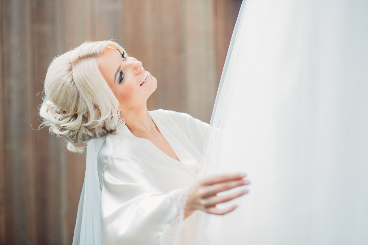 A blond bride smiling up at the sky