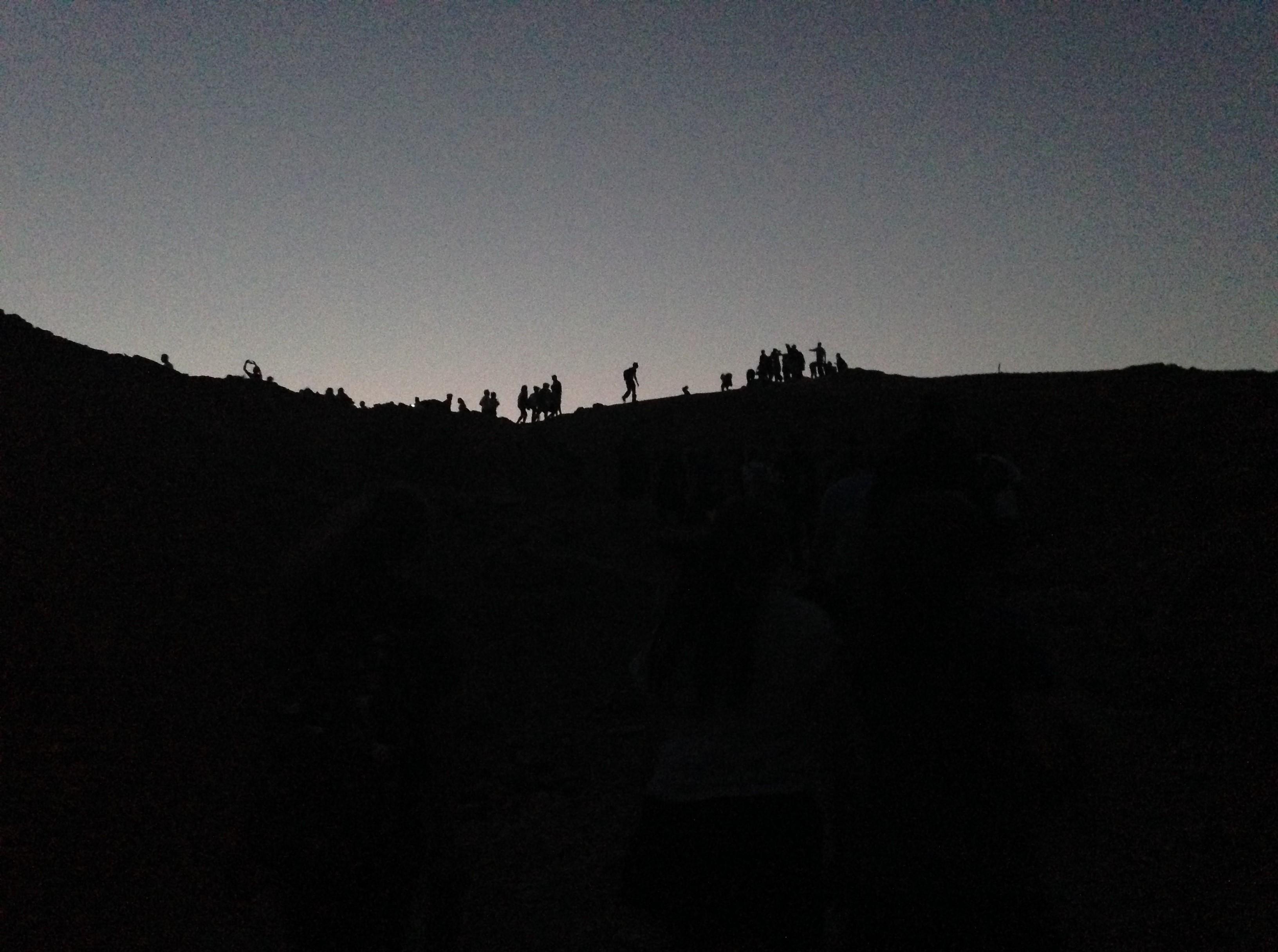 silhouette of people hiking in desert