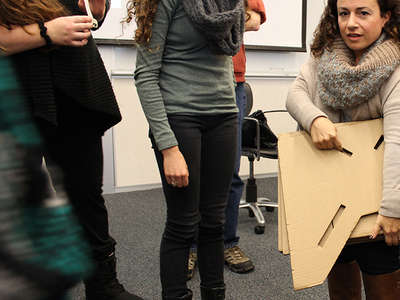 Amanda Cachia, an art historian and curator who also has dwarfism, stands with a cardboard prototype of a lectern for short stature.