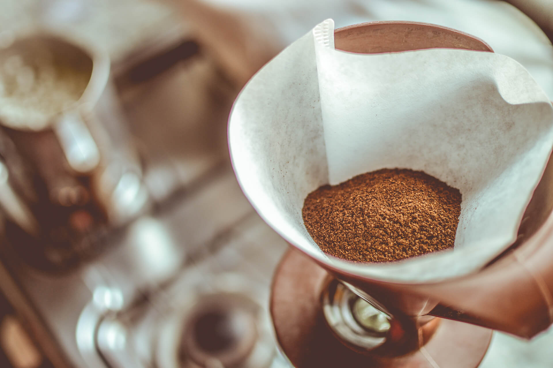 A close-up of a paper filter filled with ground coffee