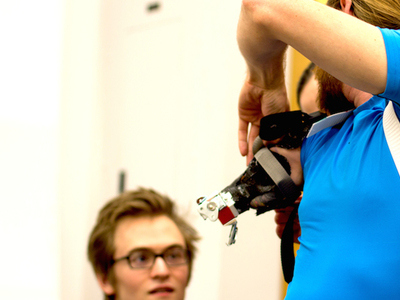Chris Hinojosa, born with one arm but not a prosthesis user, tries on an early prototype for a modular socket that would accommodate single use extensions, like one for rock climbing or biking.