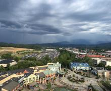 Arial view of a modern shopping complex with dark clouds in the distance.