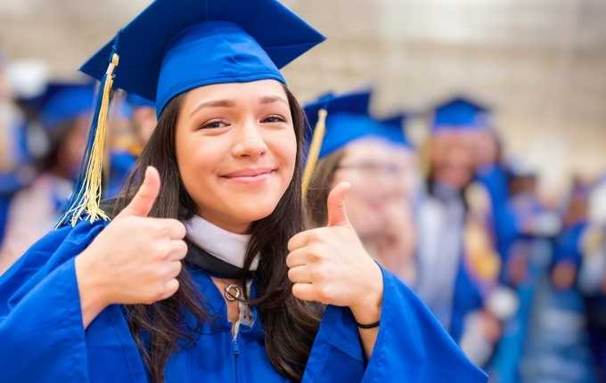A woman wearing a cap and gown smiles and gives a thumbs-up.