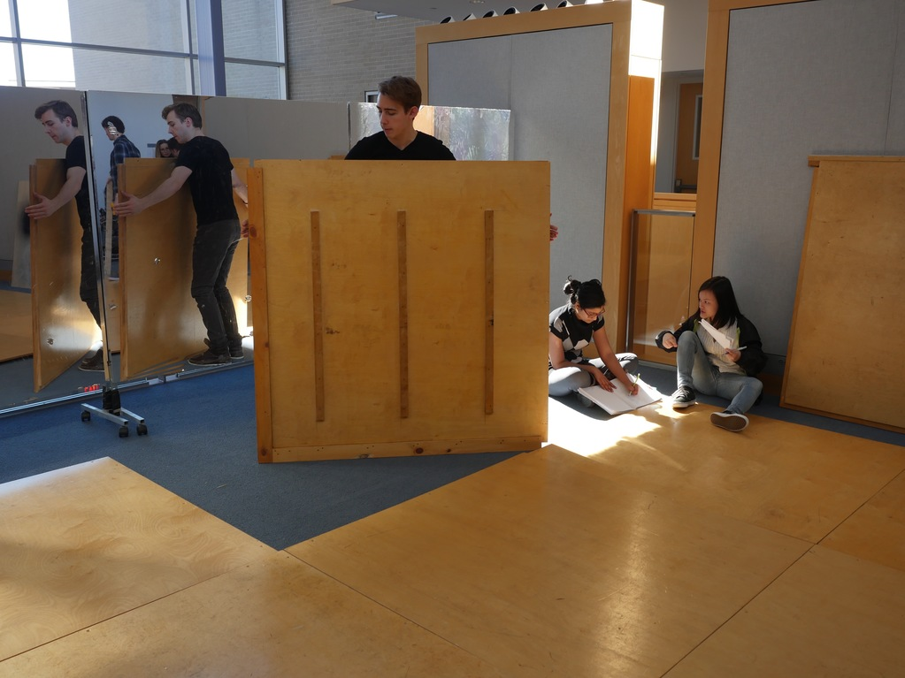 Students assemble the wood floor tiles in a modular pattern, with seven small ramps throughout.