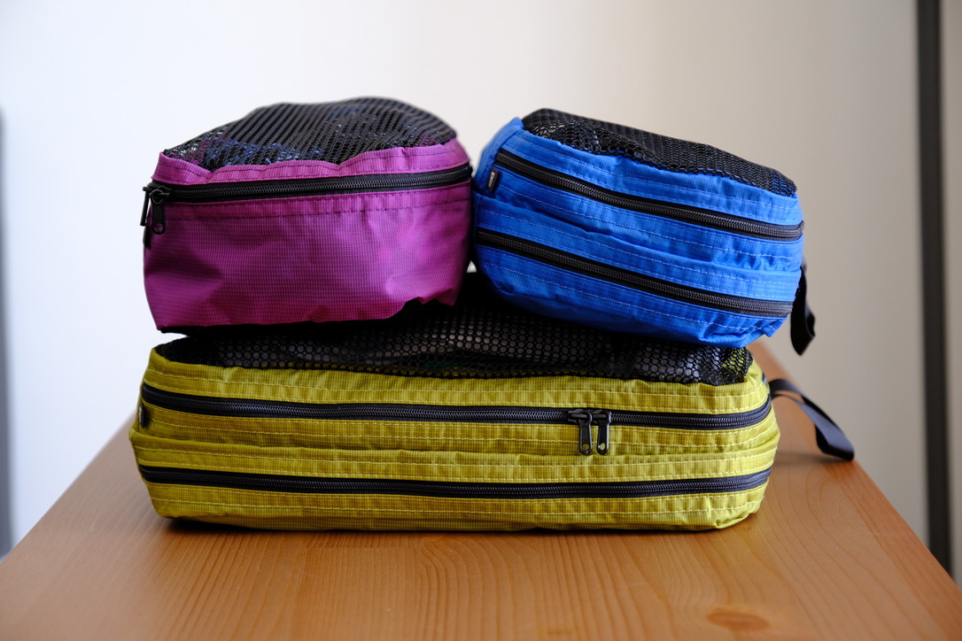 From top left to right: Small basic packing cube in Violet, Small laundry packing cube in Island (blue) and large launcy packing cube in Wasabi (yellow):