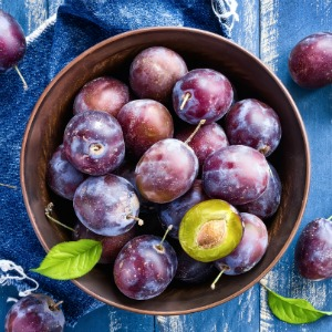 Plums on a table in a bowl