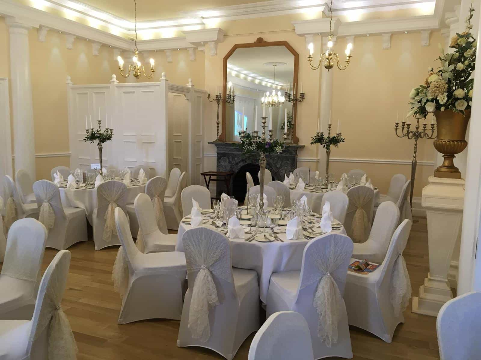 Wedding breakfast venue dressing with white table and chair linen accompanied by ivory sashes used as table runners and chair sashes
