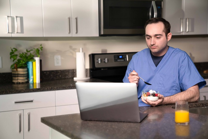 A man wearing a nurse scrub eats yogurt in his kitchen while looking at his laptop