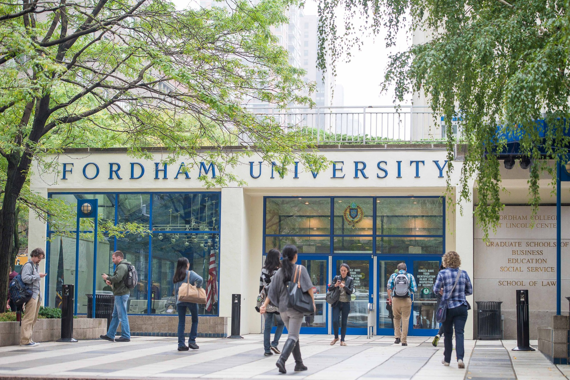 Students walking in and out of a graduate studies building at Fordham University