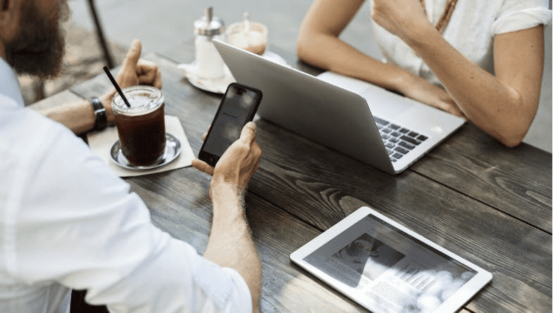 Management accountant sits at table with phone in shirt and client sits opposite on table with laptop and coffee and they discuss why management accountants are important for business #accountancy