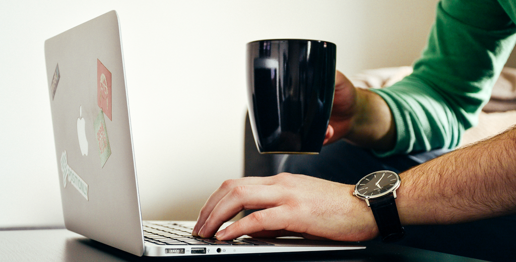 A man using a laptop and drinking a coffee