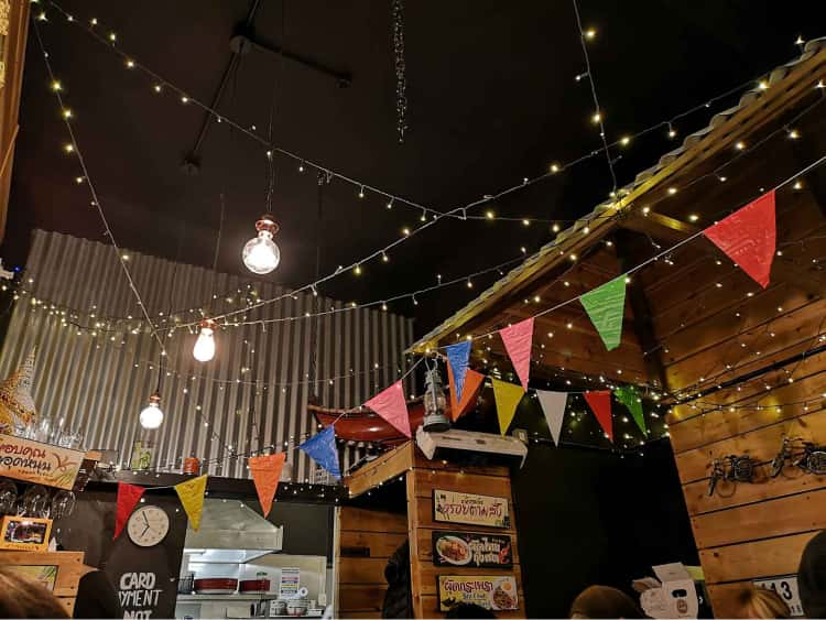 The cieling of a restaurant in York covered in multi-coloured bunting, fairy lights and large industrial light bulbs.