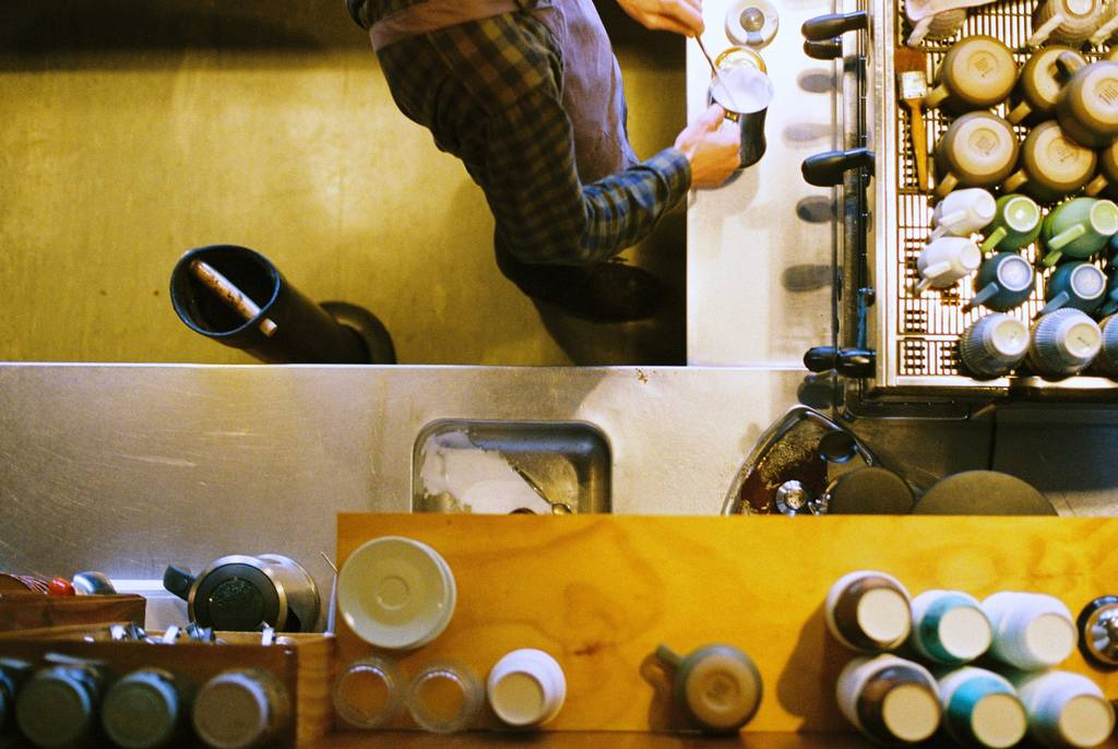 A barista makes espresso shot from directly above