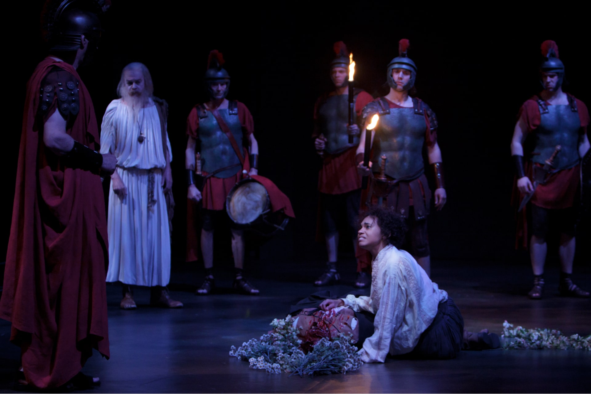 Woman cries over dead body surrounded by roman soldiers in moonlight.
