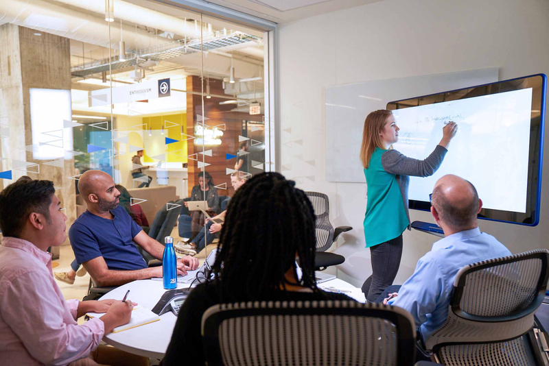 Woman writing on a digital whiteboard addresses colleagues during a meeting