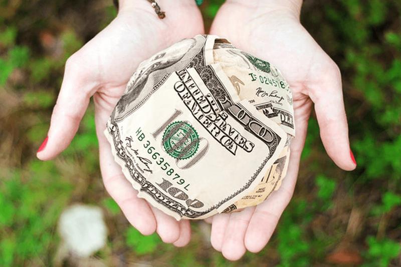 Two hands holding crumpled 100 dollar bills.