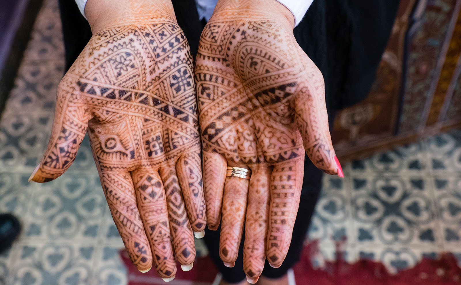 a woman's hands displaying dark henna tattoos