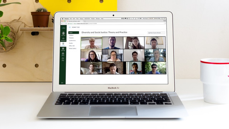 A laptop open showing a website with a web conference and people's faces