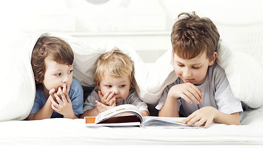 3 kids in a bed reading a book