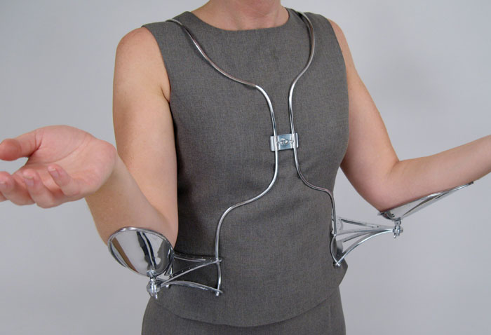 """A model wears a metal wire vestment, hung from the neck. Braces mount each side of the wearer's wait, and extensions with cups for the elbows extend to each side. The posture is an open-handed, """"unguarded"""" one."""