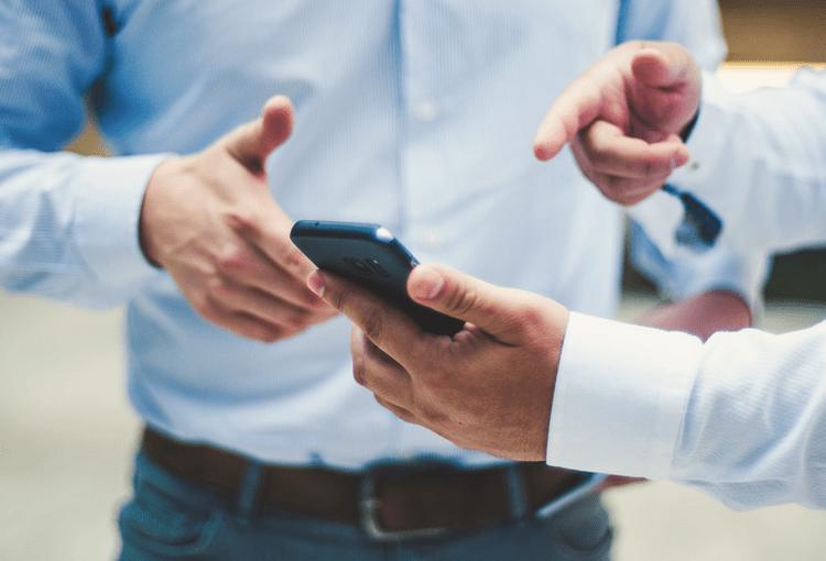 Männer in blauen Hemden zeigen auf App-Programmierung auf ihrem Smartphone