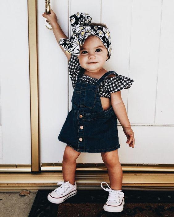 Petite fille coiffé d'un bandeau en tissu et portant une robe en jean