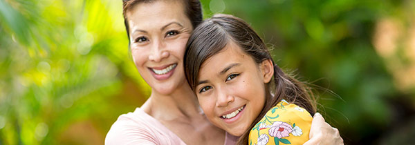A Hawaiian woman hugs her daughter.