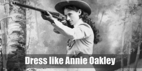 Annie Oakley wears a western styled shirt with long sleeves, a matching skirt, cowboy boots, and a cowboy hat.