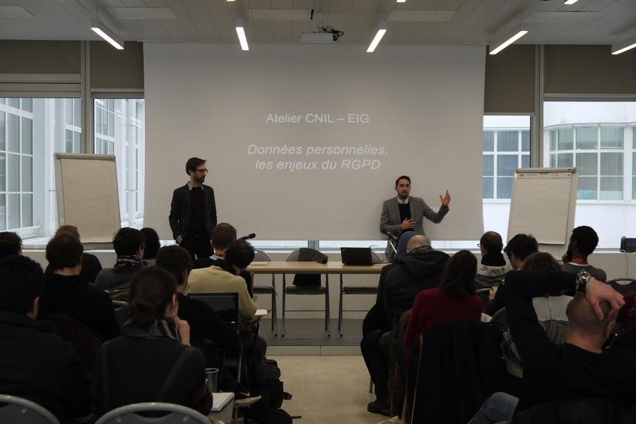 """Deux hommes présentent devant un écran blanc où est projetée une présentation qui affiche """"Atelier CNIL - EIG. Données personnelles, les enjeux du RGPD."""""""