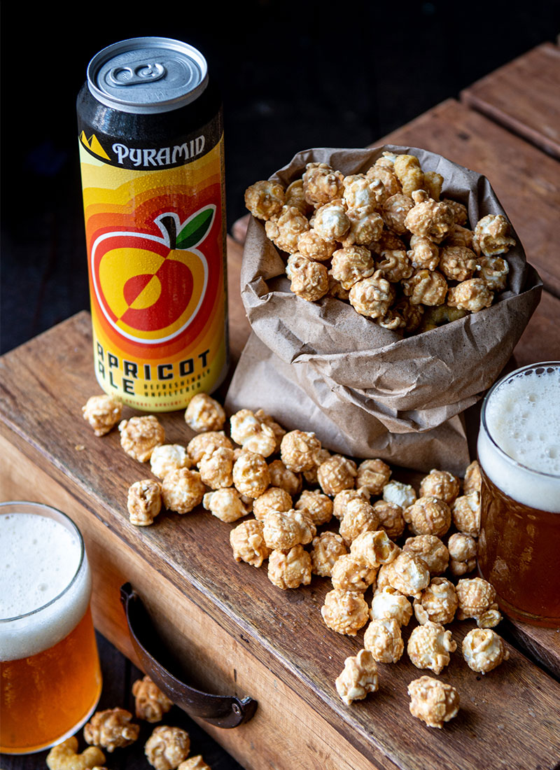 An Apricot Ale can next to a bag of caramel corn on a wooden box