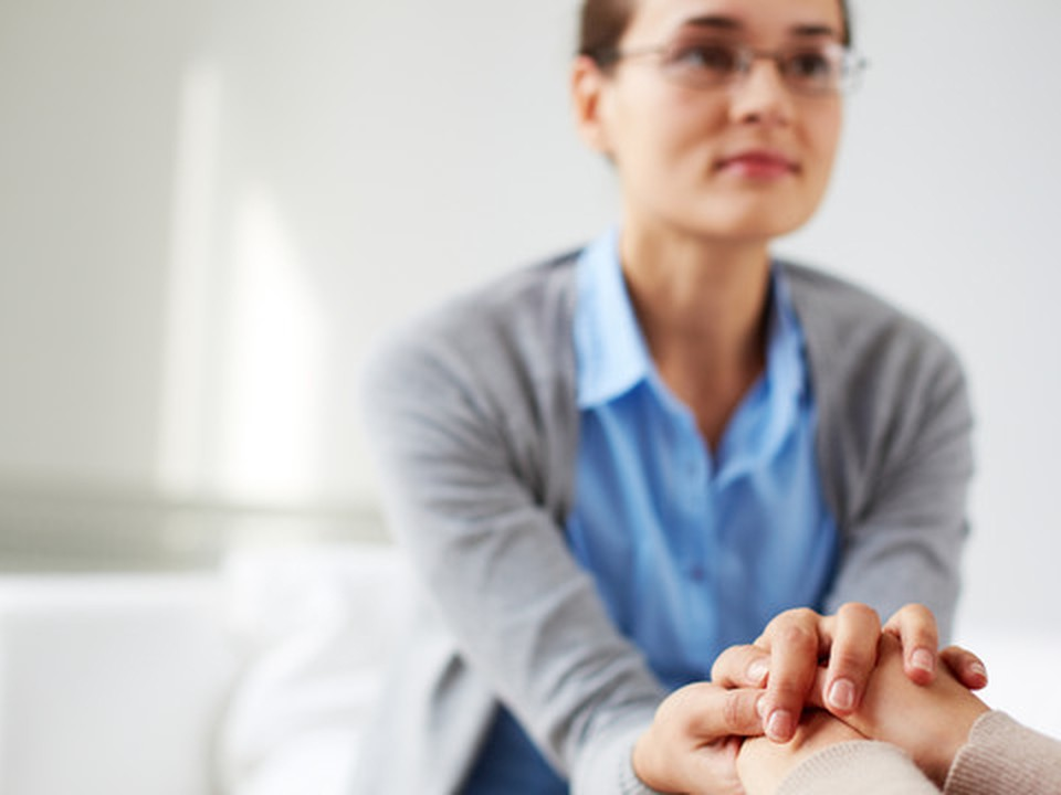A woman holding hands with other person, who is not visible on the image