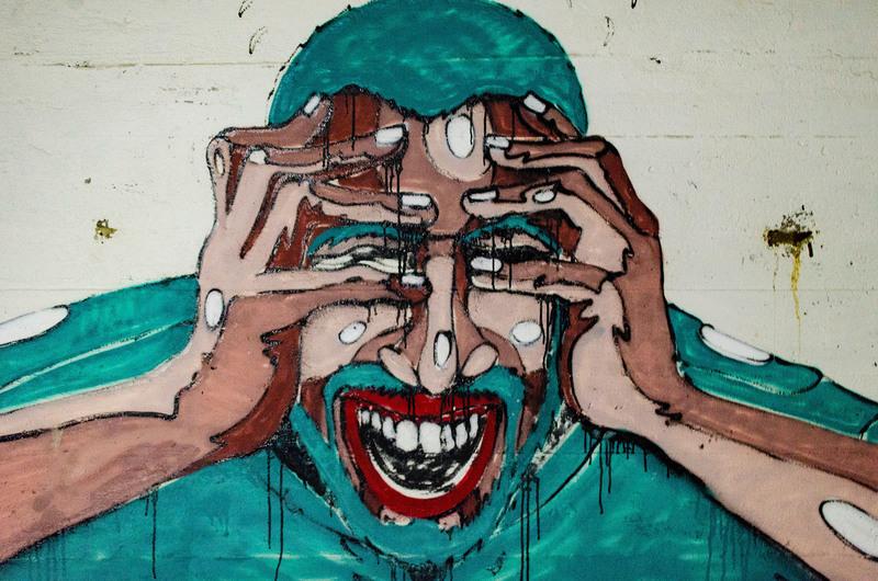 Um grafite de um homem com as mãos no rosto dando um grito.