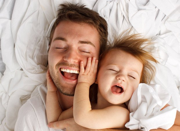 A father and baby laughing together
