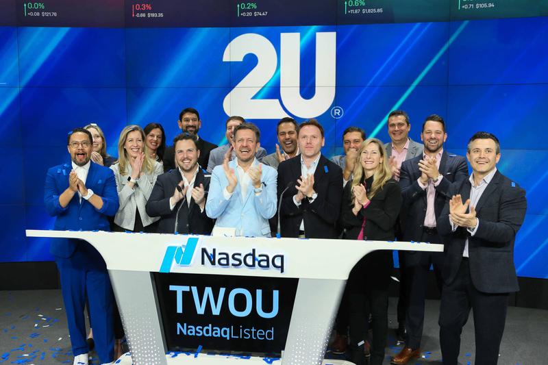 2u leadership team on stage applauding company's Nasdaq listing