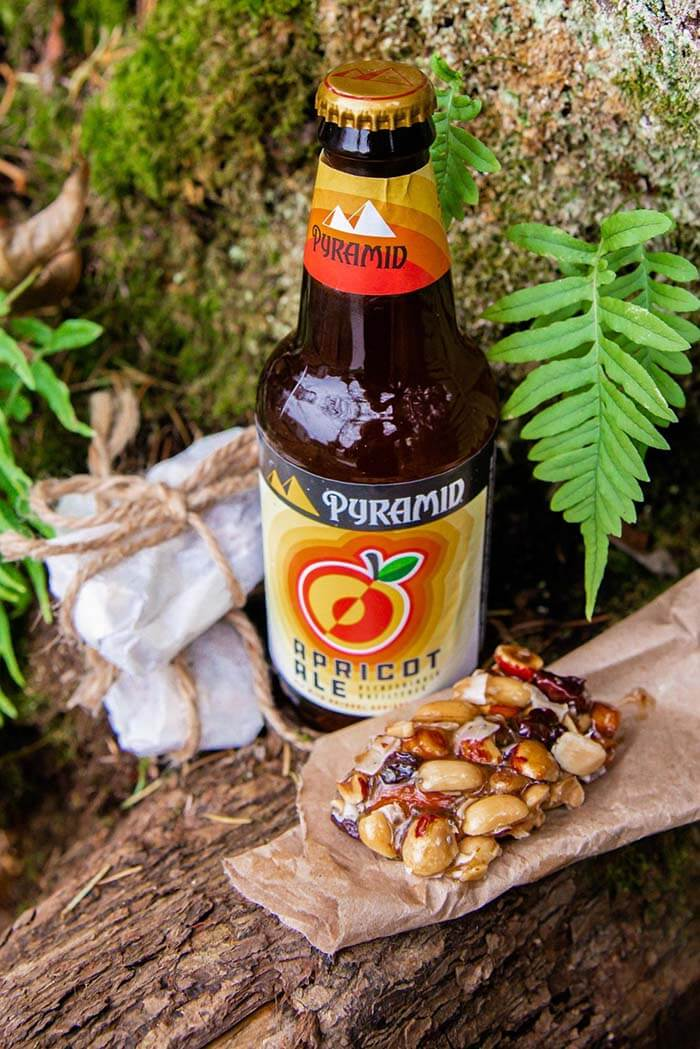 Bottle of Pyramid Apicot Ale and homemade Apricot Ale Trail Bars photographed outdoors on a nature trail