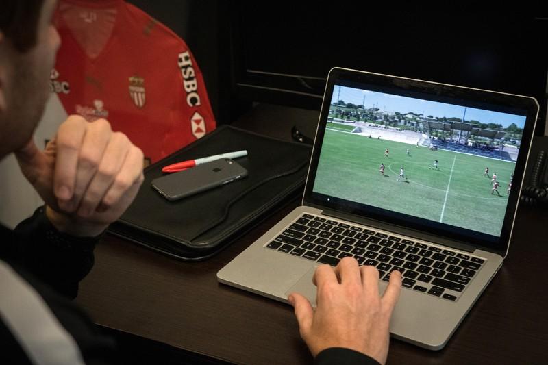 ノート PC でサッカー映像を見ているアナリスト