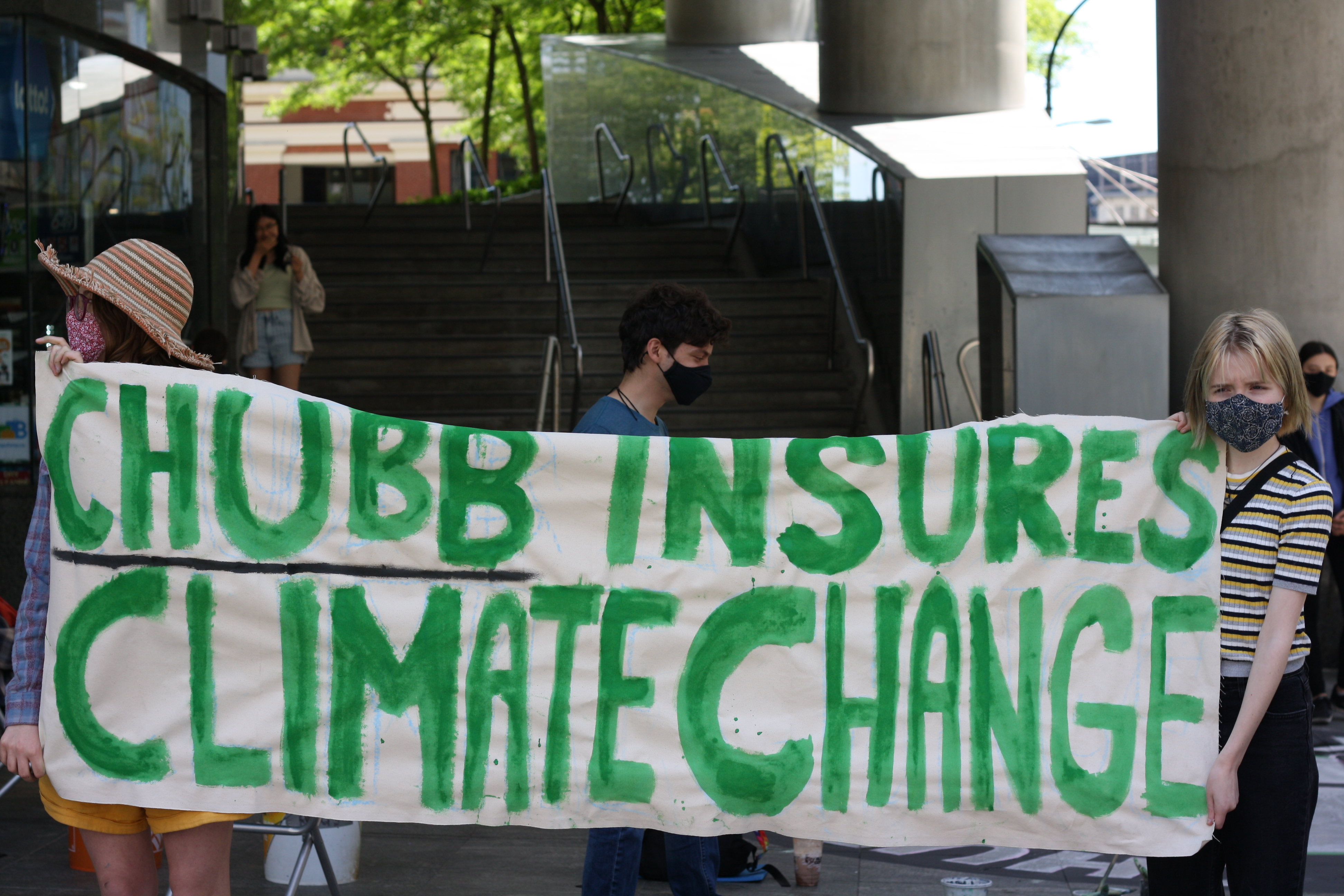 Sustainabiliteens members holding up a poster outside of the Downtown Vancouver Chubb Insurancing office, stating Chubb Insures Climate Change.