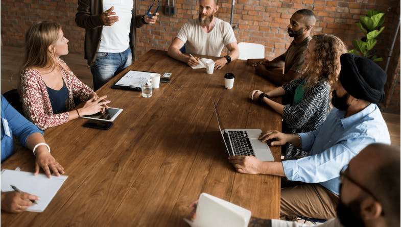 Business owner, boss talks to colleagues, team about the importance of training in the workplace over a wooden table with laptops, documents, tablets, notepads #business #staff