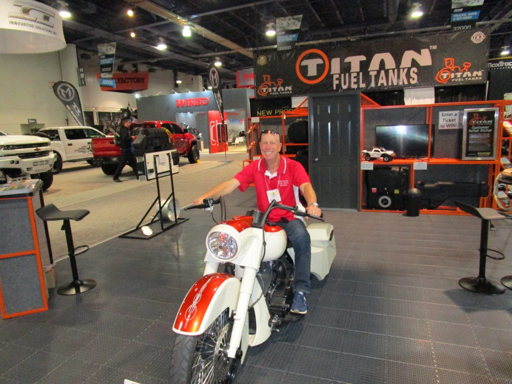 Adam Scheps sitting on a White and Red Motorcycle
