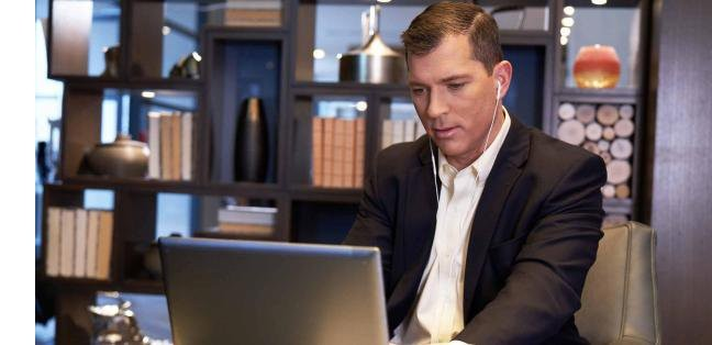 Man in a black blazer types on his laptop while listening to earbuds during a coffee break
