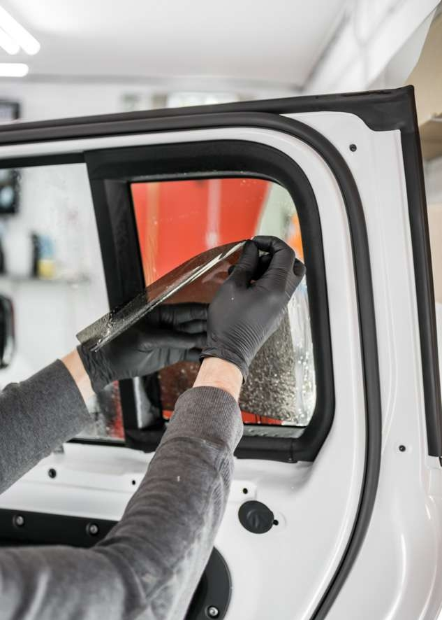 White Land Rover Defender car rear window being tinted