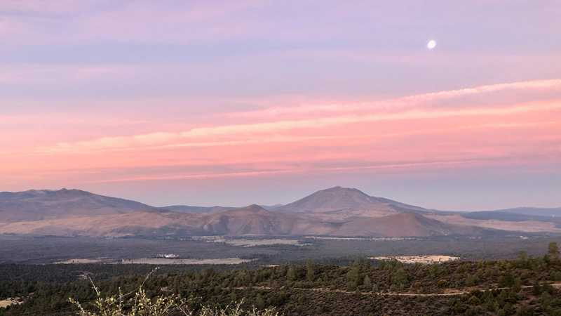 The moon hangs over Burney Mountain at sunrise