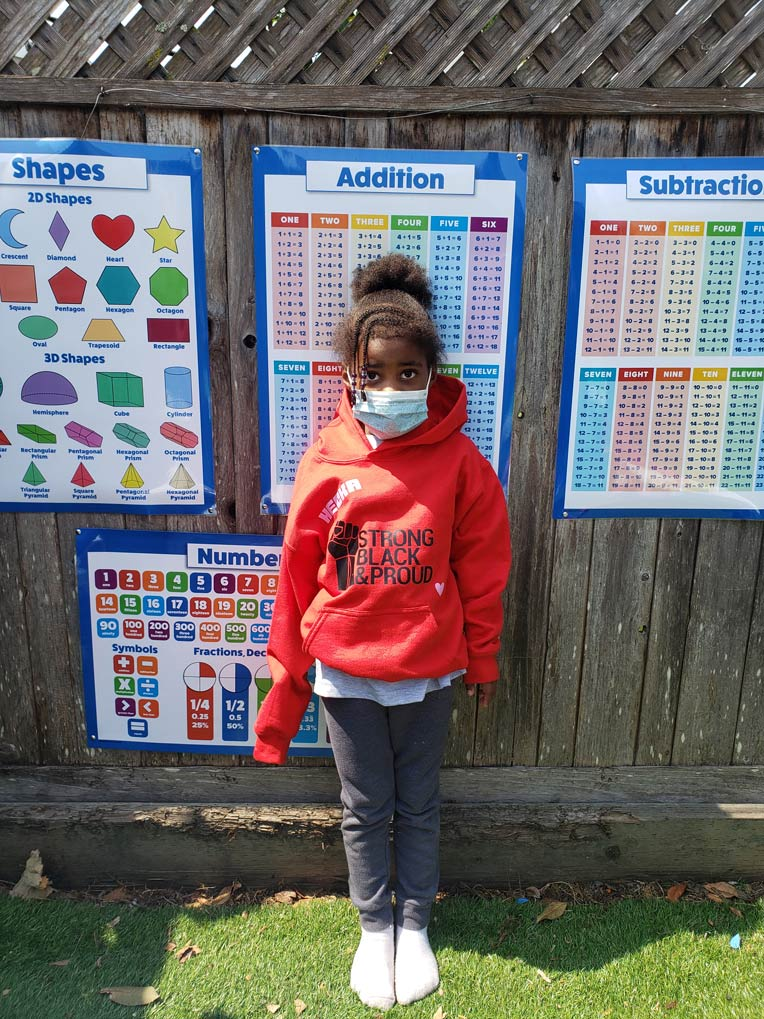 """A young Black female student standing in front of addition and subtraction table posters, wearing a red """"STRONG, BLACK, PROUD"""" hoodie"""