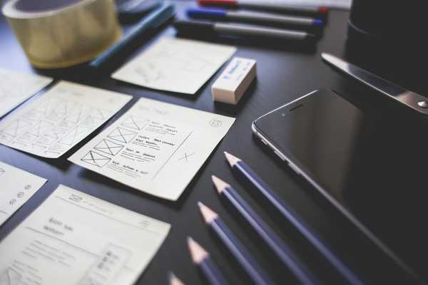 Picture of a desk with writing tools and notes that have a design concept for different views of a web application.