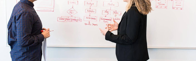 Trainerin an Whiteboard während eines Workshops