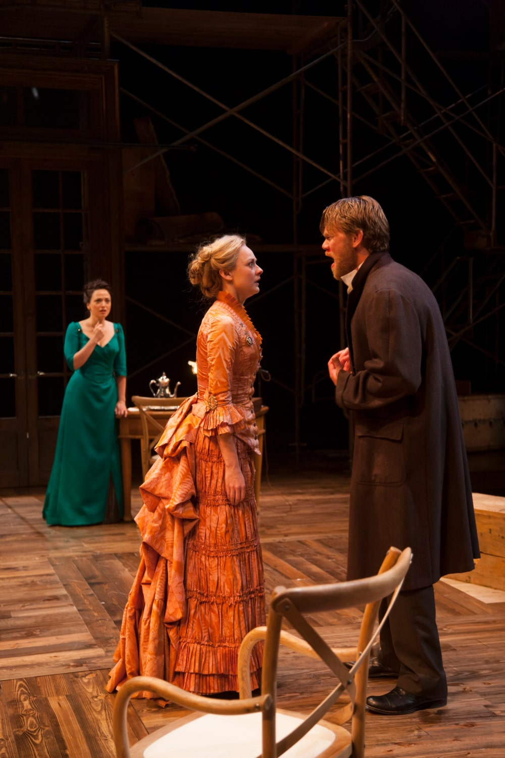 Woman in orange layered gown argues with bearded man in long coat, with green-dressed woman watching behind.