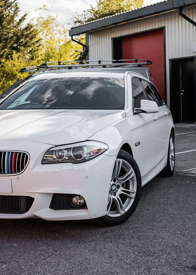 Front side shot of white BMW 5 series with tinted windows