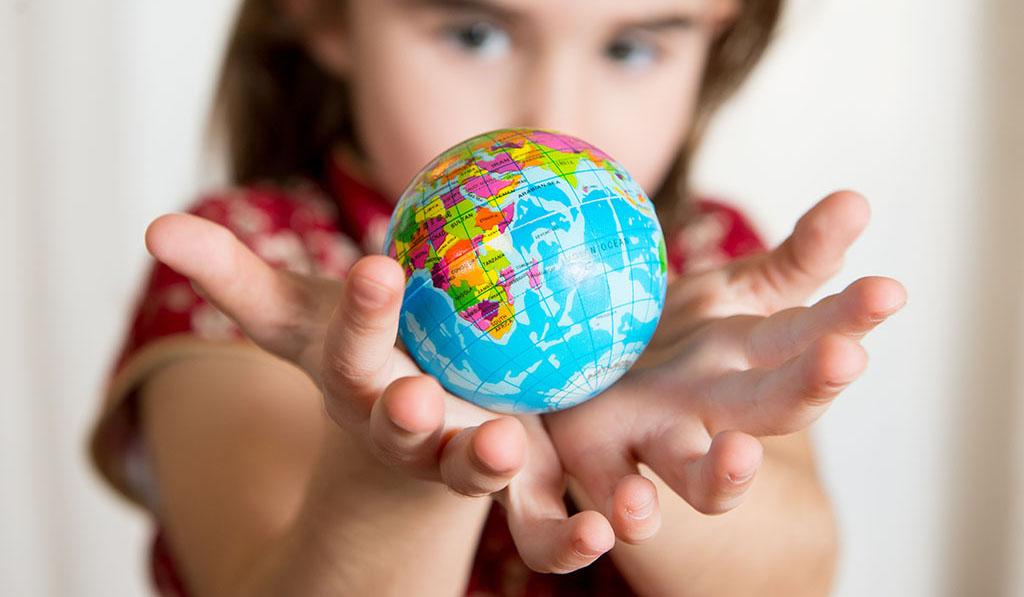 World explorer girl playing with globe