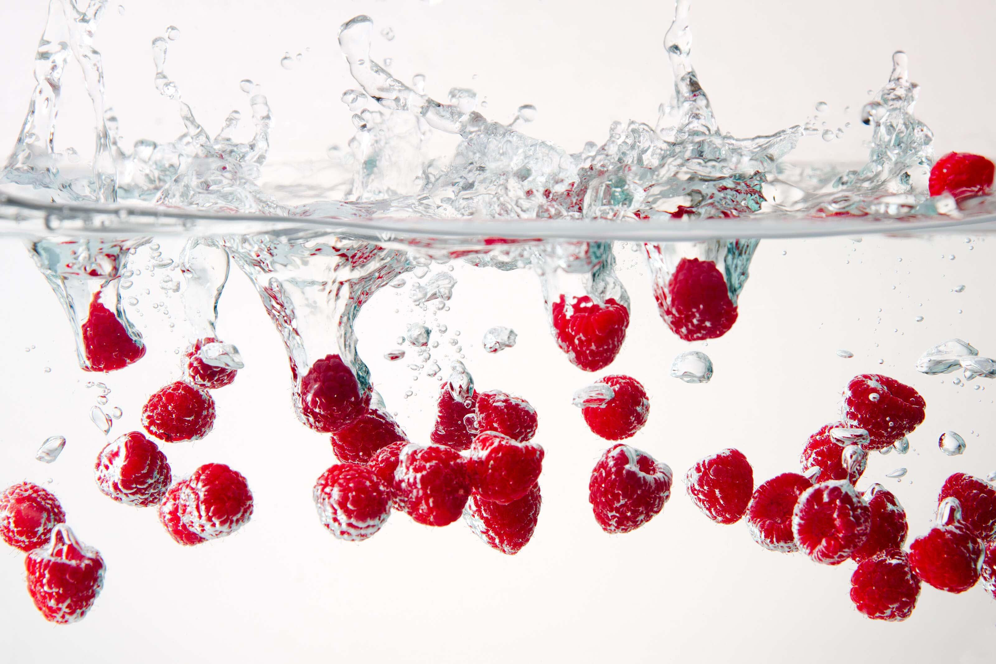 raspberries splashing into water